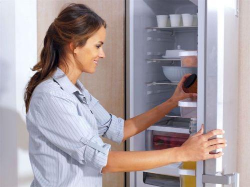 Женщина что-то кладет в холодильник