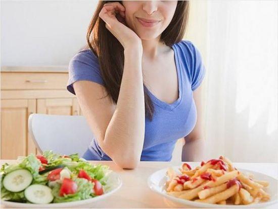 Женщина выбирает между тарелками с едой