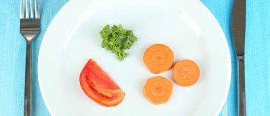 Дольки помидора, моркови и зелень на тарелке