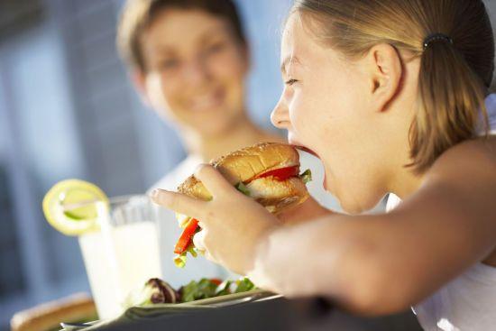 Девочка ест гамбургер