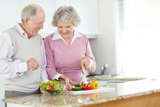 Пожилая пара готовит еду